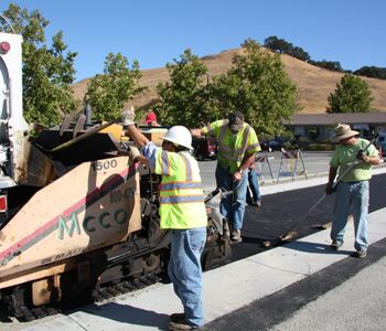 Photo of roadwork. Several men are working to spread asphalt as the truck moves slowly along the roa