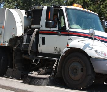 Side view of a street sweeper moving down the street. The shot is close in so you can see the front
