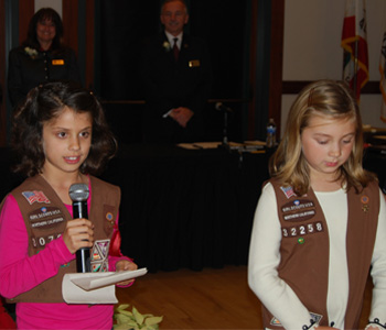 Two Girl Scouts reading the pledge of allegiance