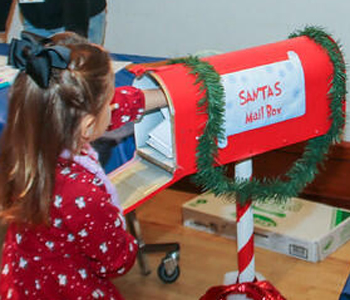 Little girl posting mail to Santa's Mail Box