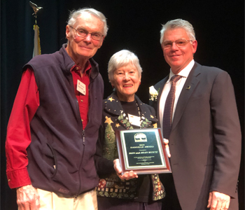 Don and Joan Kurtz and their community service award with Robert Storer