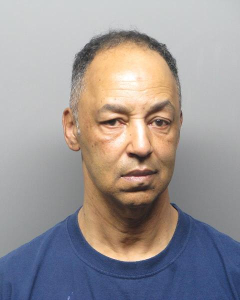 Photo of Ramon Pruitt, wearing dark navy shirt standing before a grey background