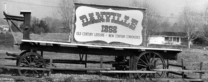 A black and white photo of an old wagon and a sign for Danville dated 1858