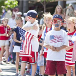 Child holding an american flag with other kids in the background